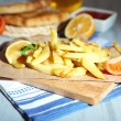 Stock Photo: Ruddy fried potatoes on wooden board on table close-up