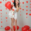 Attractive young woman with rose and balloons in room on Valentine Day — Stock Photo #40848623