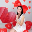 Attractive young woman with big heart and balloons in room on Valentine Day — Stock Photo #40848645