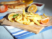 Ruddy fried potatoes on wooden board on table close-up — Stok fotoğraf