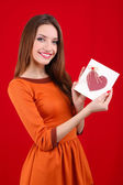 Attractive woman with postcard, on red background — Stok fotoğraf