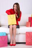 красивая молодая женщина, сидя на диване с сумки и подарочные коробки на сером фоне — Стоковое фото