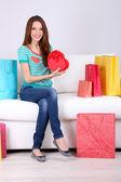 Bela jovem sentada no sofá com sacos de compras e caixa de presente em fundo cinza — Fotografia Stock