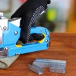 Fastening fabric and board using construction stapler on bright background — Stok Fotoğraf #40884417