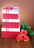Schöne geschenk-boxen mit blumen auf tisch mit braunen hintergrund — Stockfoto