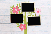 Holder in form of tree with instant photo cards on color wooden background — Stok fotoğraf