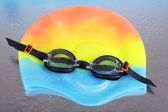 Swim cap and goggles on silver background — Stock Photo