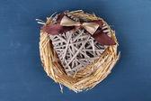 Corazón decorativo en el nido, sobre fondo de madera color — Foto de Stock