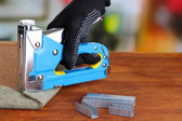 Fastening fabric and board using construction stapler on bright background — Stok fotoğraf