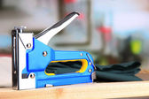 Construction stapler with fabric on cork board on bright background — Stockfoto