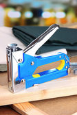 Construction stapler with fabric on cork board on bright background — Foto de Stock