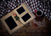 Composition with coffee cup, plaid, and photo album, on wooden background — Foto Stock