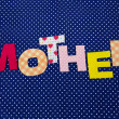 Mother- lettering of handmade paper letters on blue polkbackground — Stock Photo #40891883