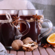 Stock Photo: Mulled wine with lemon and nuts on table on fabric background