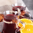 Stock Photo: Mulled wine with oranges and spices on table on fabric background
