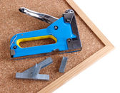 Construction stapler and staples on cork board close up — Stock Photo