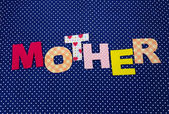 Mother- lettering of handmade paper letters on blue polka background — Stock Photo