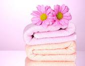 Ręczniki i piękne kwiaty na różowym tle — Zdjęcie stockowe