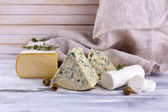 Different tasty cheese, on wooden table — Stok fotoğraf