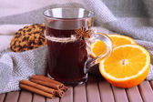 Mulled wine with oranges and spices on table on fabric background — Stock Photo