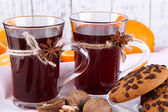 Mulled wine with oranges and cookies on table on wooden background — Stock Photo