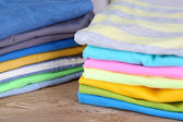 Stack of colorful clothes, on wooden background — Foto Stock