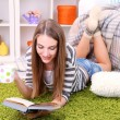 Young woman resting with book on fluffy carpet, near sofa at home — Stock Photo #40932891