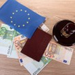 Stock Photo: Gavel, money, passport and flag of Europe, on wooden background