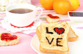 Delicious toast with jam and cup of tea on table close-up — Stock Photo