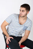 Handsome young man sitting on chair on light background — Stock Photo