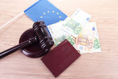 Gavel, money, passport and flag of Europe, on wooden background — Stock Photo