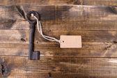 Chiave con tag vuoto, sul colore di sfondo in legno — Foto Stock