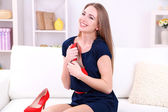 Girl sitting on sofa with sexy red shoes, on home interior background — ストック写真