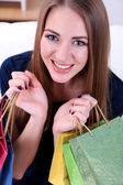 Beautiful young girl sitting on sofa with shopping bags, close-up — Stock Photo
