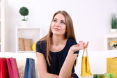 Beautiful young girl sitting on sofa with shopping bags on home interior background — Stock Photo