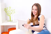 Young woman resting with tablet on sofa at home — Stock Photo