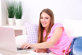 Young woman resting with laptop on sofa at home — Stock Photo