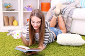 Young woman resting with book on fluffy carpet, near sofa at home — Stock Photo
