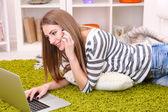 Junge Frau mit Laptop im Erdgeschoss in der Nähe von Sofa zu Hause ausruhen — Stockfoto