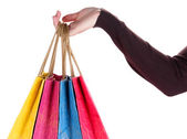 Colorful shopping bags in female hand, isolated on white — Stock Photo