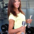 Pretty sporty girl with dumbbells in gum — Stock Photo