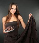 Retrato de muchacha joven hermosa con dulces de chocolate sobre la placa en fondo gris — Foto de Stock