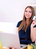 Young woman sitting with laptop on sofa and holding credit card in her hand, at home — Stock Photo
