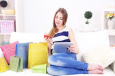 Young woman sitting with tablet on sofa and holding credit card in her hand, at home — Stockfoto