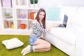 Young woman resting with laptop on floor near sofa, at home — Stock Photo