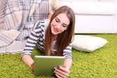 Young woman resting with tablet on floor near sofa, at home — Stock Photo
