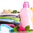 Stock Photo: Detergent with washing powder and pile of colorful clothes isolated on white