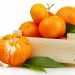 Ripe tasty tangerines with leaves in wooden box isolated on white — Stock Photo #40994191