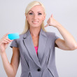 Business woman with visiting card on grey background — Stock Photo