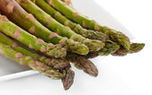 Delicious fresh asparagus on a plate isolated on white — Stock Photo